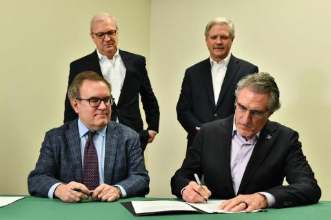 two men signing paperwork and two men standing in the background